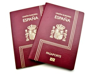 Two passports from Spain in red, surrounded by white background